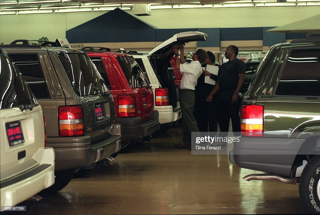 FAuto#50610sc2$A Customer Checks Out The Trunk Area Of A New Grand Cherokee