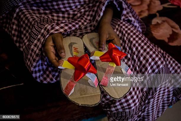 Fauziah a Sudanese asylum seeker shows her handmade sandals made from cardboard in Kolekta hotel where hundreds of refugees and asylum seekers stay...