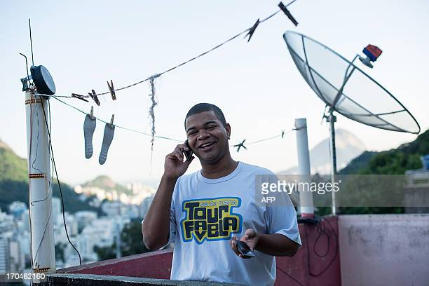 Favela tour guide Thiago Firmino speaks on his cell phone in Santa Marta shantytown in Rio de Janeiro Brazil on June 11 2013 AFP PHOTO / YASUYOSHI...