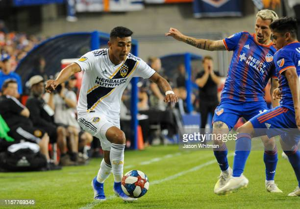 Favio Alvarez of the LA Galaxy attempts to move the ball past FC Cincinnati defenders during the second half of their MLS match at Nippert Stadium on...