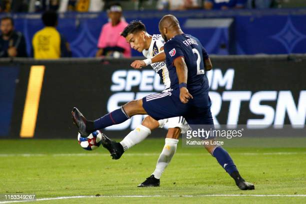 Favio Alvarez of the Los Angeles Galaxy and Andrew Farrell of New England Revolution fight for control of the ball during the second half of a game...