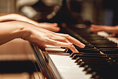 Favorite classical music...Close up view of gentle female hands playing a melody on piano while taking piano lessons