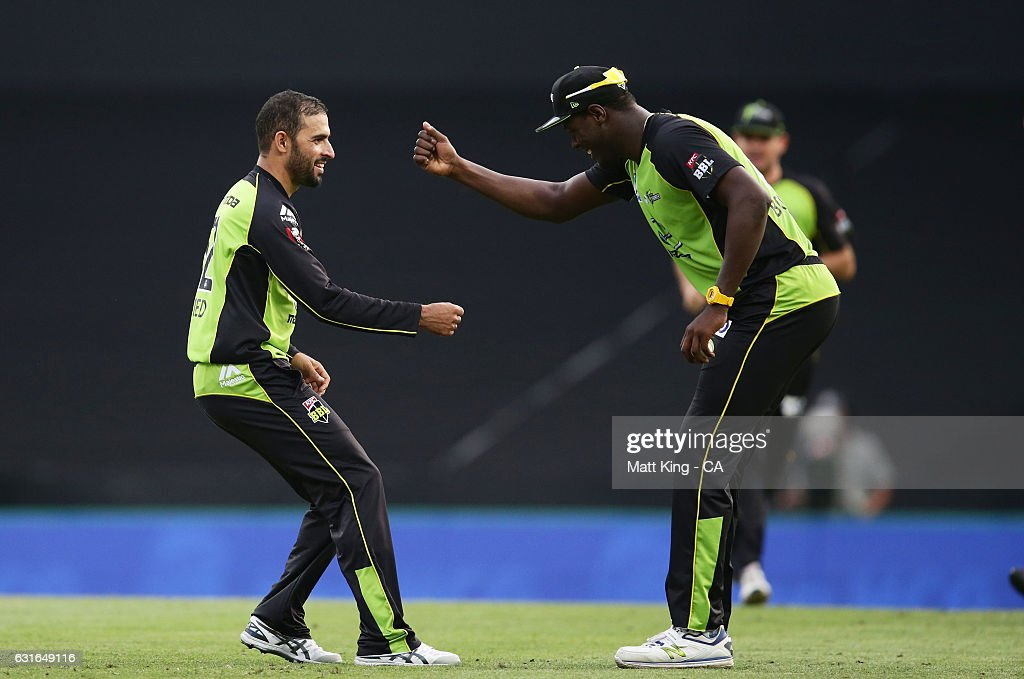 Fawad Ahmed of the Thunder (L) celebrates with Carlos Brathwaite (R) after taking the wicket of Sean Abbott of the Sixers during the Big Bash League match between the Sydney Sixers and the Sydney Thunder at Sydney Cricket Ground on January 14, 2017 in Sydney, Australia.