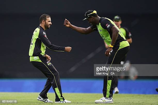 Fawad Ahmed of the Thunder celebrates with Carlos Brathwaite after taking the wicket of Sean Abbott of the Sixers during the Big Bash League match...