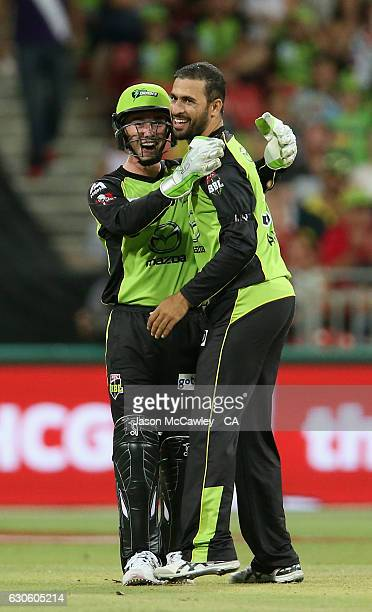 Fawad Ahmed of the Thunder is congratulated by during Jake Doran after dismissing Ben Cutting of the Heat the Big Bash League match between the...