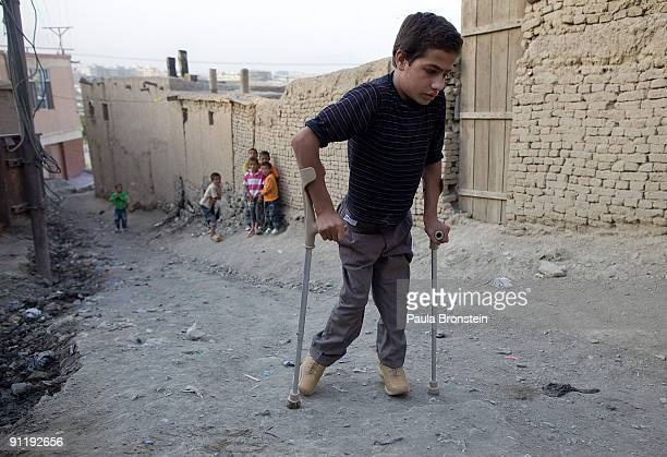 Fawad Rahmani makes his way home using his crutches and special braces fitted from the ICRC Orthopedic clinic on September 26, 2009 in Kabul,...
