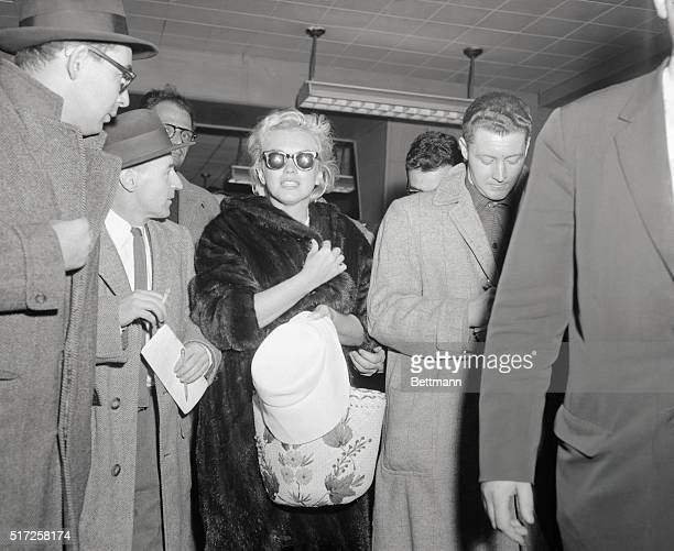 Fawn like without makeup hatless and her hair windblown sun tanned actress Marilyn Monroe is besieged by reporters at Idlewild Airport after her...