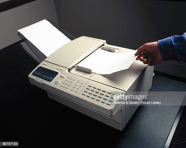 A fax machine reads an image from one piece of paper then sends the image over a telephone line where another fax machine receives it and prints out...