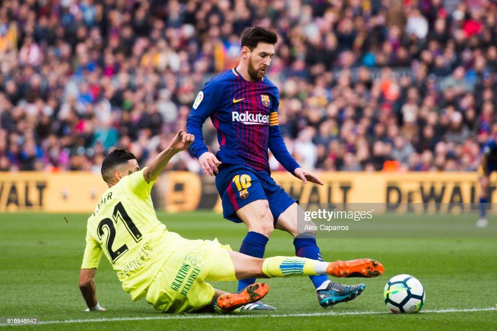 Faycal Fajr of Getafe CF tackles Lionel Messi of FC Barcelona during the La Liga match between Barcelona and Getafe at Camp Nou on February 11, 2018 in Barcelona, Spain.