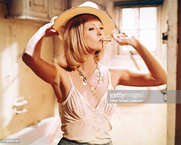 Faye Dunaway US actress smoking a cigarette while trying a hat on in a publicity image issued for the film 'Bonnie and Clyde' 1967 The crime drama...