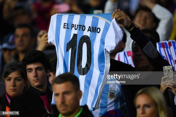 A fcb supporter holds up an Argentina national team shirt with the number 10 of Lionel Messi during the La Liga match between Barcelona and SD Eibar...