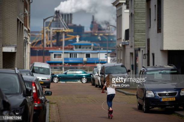 Fchild on a scooter in a residential area near the Tata Steel plant on August 22, 2021 in Ijmuiden. The Tata steel plant is under investigation by...