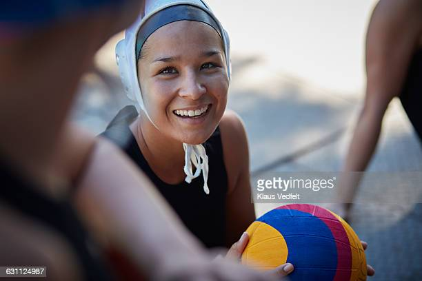 Feamle waterpolo player laughing & holding ball