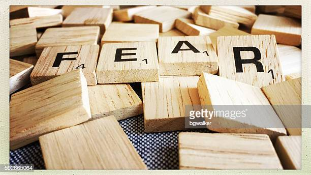 fear spelled with scrabble tiles - game night stock photos and pictures