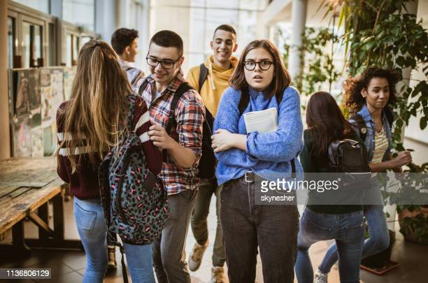 fearful student among her classmates in a school hallway. - stereotypical stock pictures, royalty-free photos & images