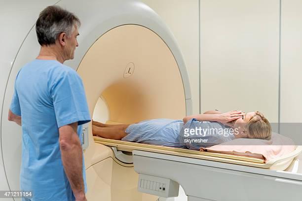 Fearful woman having a medical exam via MRI scan.