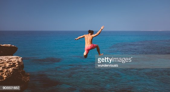 Fearless cliff diver diving into tropical island sea