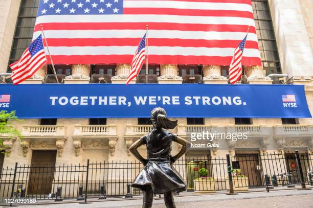 Fearless Girl statue wears a face mask outside New York Stock Exchange during the coronavirus pandemic on May 25, 2020 in New York City. Government...