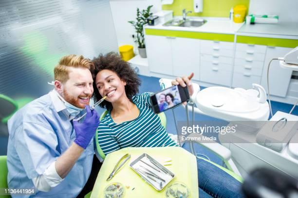furchtlose patientin, die zahnophobie überwindet, ein selfie mit ihrem zahnarzt nimmt, bevor sie eine betäubungsspritze mit einer spritze erhält - dentist phobia stock-fotos und bilder