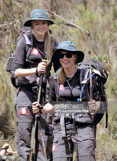 Fearne Cotton looks on as Denise Van Outen holds up a broken pole after falling over as they trek up Kilimanjaro on the second day of The BT Red Nose...
