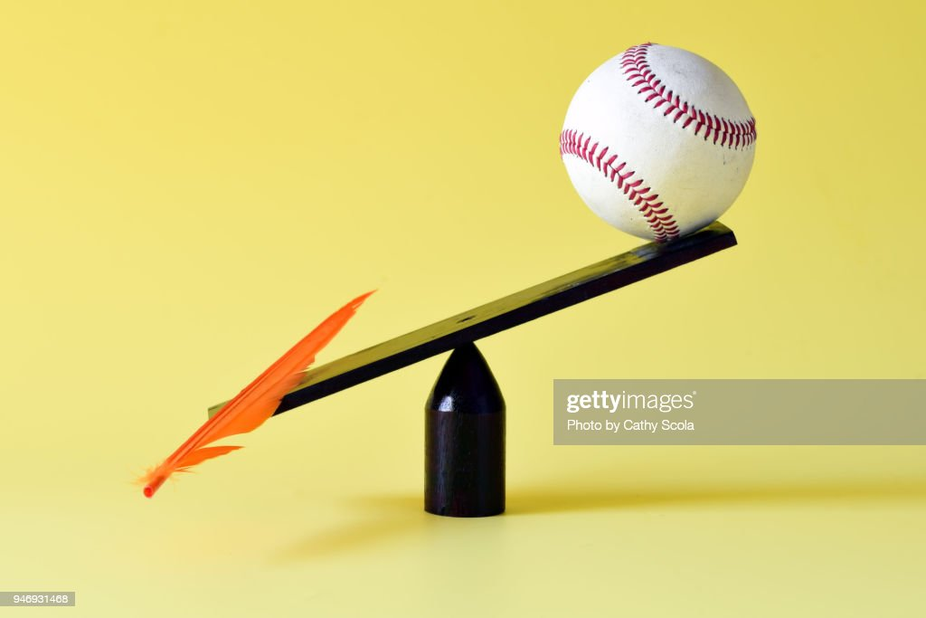 Feather and baseball on scale : Stock Photo