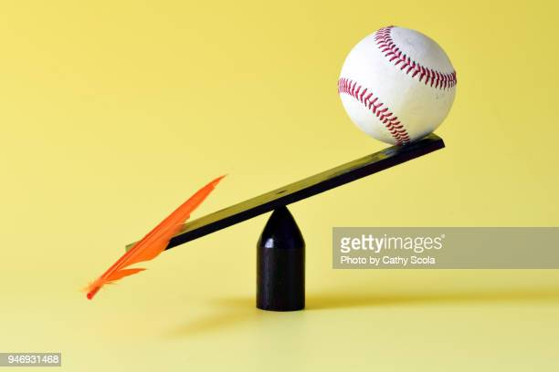 feather and baseball on scale - imbalance stock pictures, royalty-free photos & images