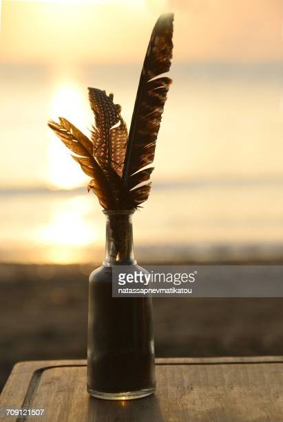 Feathers in a glass bottle on beach