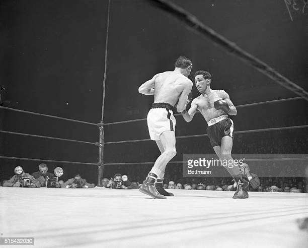 Featherweight champ Willie Pep is shown landing a hard right to French challenger Ray Famechon's midsection during tonight's 15round title bout at...