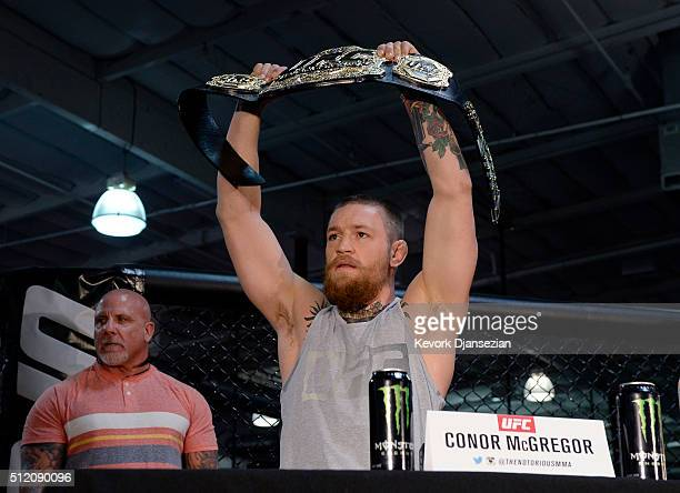 UFC featherweight champion Conor McGregor holds up the championship belt during a news conference with lightweight contender Nate Diaz at UFC Gym...