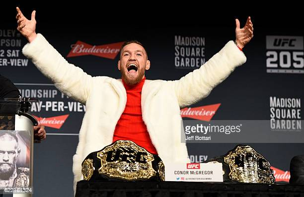 UFC featherweight champion Conor McGregor of Ireland takes the belt of lightweight champion Eddie Alvarez during the UFC 205 press conference inside...