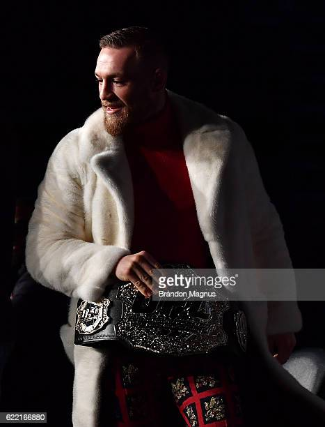 UFC featherweight champion Conor McGregor of Ireland takes the belt of UFC lightweight champion Eddie Alvarez during the UFC 205 press conference...