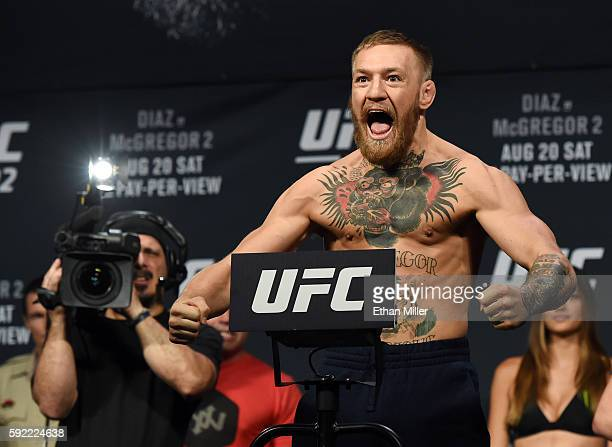 UFC featherweight champion Conor McGregor poses on the scale during his weighin for UFC 202 at MGM Grand Conference Center on August 19 2016 in Las...