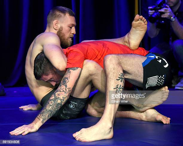 UFC featherweight champion Conor McGregor works out with his head coach John Kavanagh during an open workout for UFC 202 at Rocks Lounge at the Red...