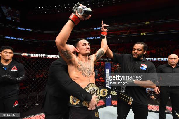 Featherweight champion Max Holloway celebrates after defeating Jose Aldo of Brazil in their UFC featherweight championship bout during the UFC 218...