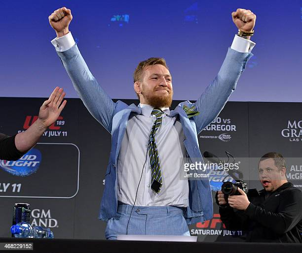 UFC featherweight title challenger Conor 'The Notorious' McGregor reacts to fans cheers after grabbing the belt away from UFC Featherweight Champion...