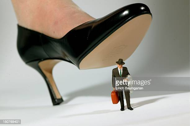 Feature dominance of women competition between men and women emanzipation Shoe of a woman with high heels standing on a figure of a manager
