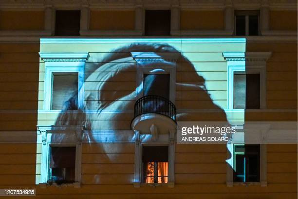 A feature film is projected on the facade of a building in Rome on March 17 2020 as part of a Cinema from Home event by the association Alice in the...