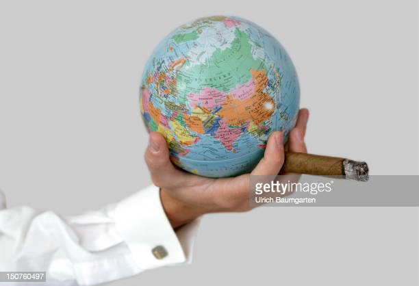 Feature globalization Hand of a manager with a cigar and a globe