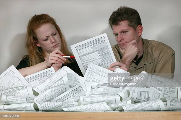 Feature inscrutable application forms for the Arbeitslosengeld II Young couple with the forms for the Arbeitslosengeld II