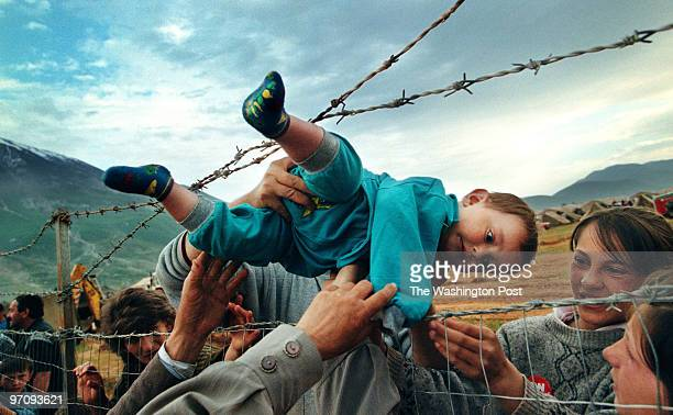 Feature Photography Pulitzer Prize May 3 1999 Kosovar refugee Agim Shala 2 years old is passed through the barbed wire fence into the hands of...