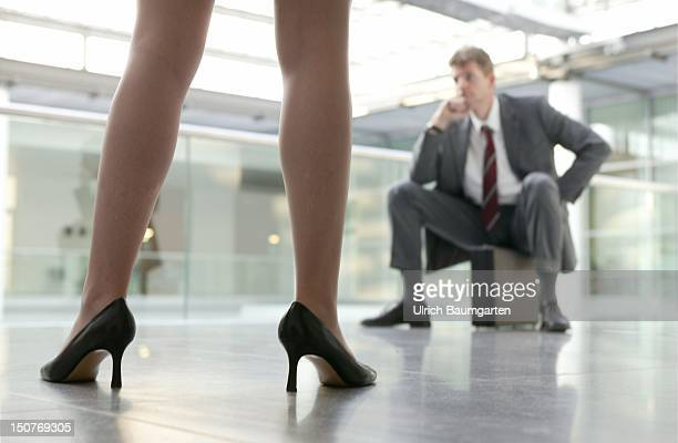 Feature women in the professional life competition man woman businesswoman Manager in a suit sitting on a briefcase In the front the legs of a woman