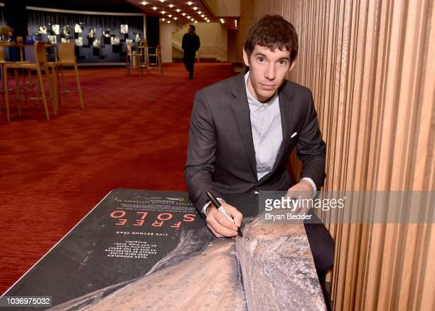 Featured Free Soloist Alex Honnold signs posters during the New York City premiere of National Geographic Documentary Films' 'Free Solo' at Jazz at...