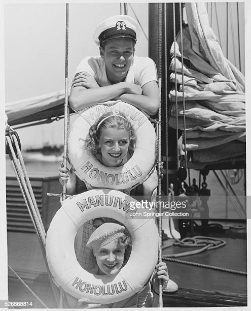 Featured players William Henry, Betty Furness, and Ruth Channing relax on a sailboat while taking a break from films.