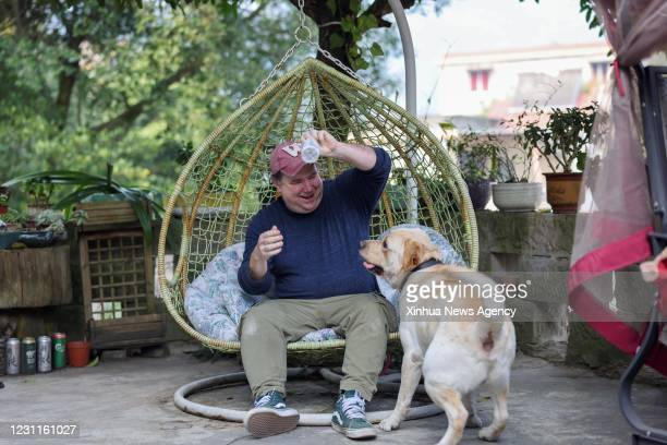 Feb. 10, 2021 -- Benjamin interacts with a pet dog outside the house of his wife's relatives in Chongqing, southwest China, Feb. 10, 2021. Benjamin,...