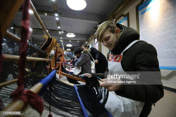 BEIJING Feb 13 2019 Foreign tourists experience tapestry weaving of Tujia ethnic group in Wulingyuan District of Zhangjiajie City central China's...