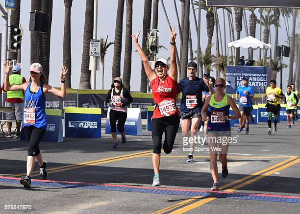 LOS ANGELES Feb 14 2016 Diane Villa of Chino CA dances across the finish line on Ocean Ave in Santa Monica California at the end of the LA Marathon...