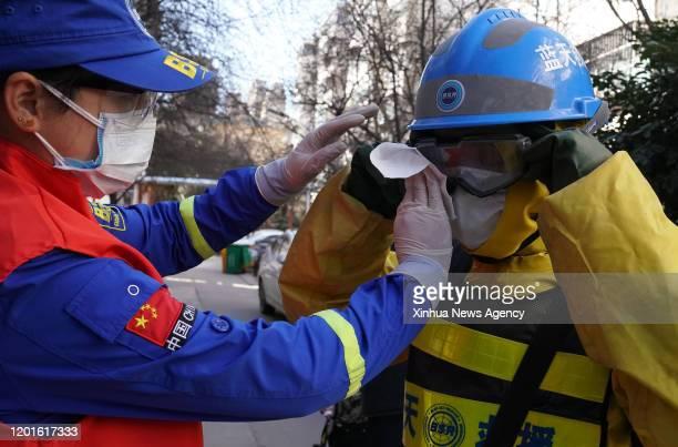 Feb. 16, 2020 -- Volunteer Huang Jun L, a member of the Zhengzhou Blue Sky Rescue team, helps her husband Li Jian wipe the goggles during a...