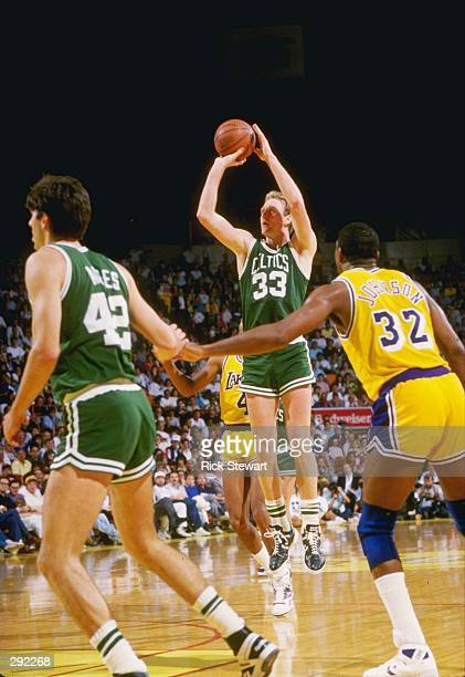 Guard Larry Bird of the Boston Celtics shoots the ball as Magic Johnson of the Los Angeles Lakers shoots the ball during a game at the Great Western...