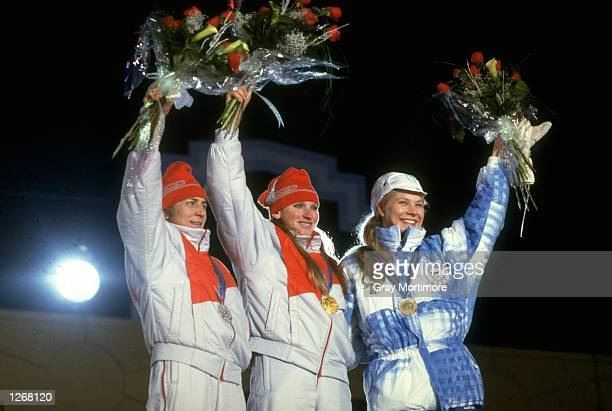 Raisa Smetania of USSR Vida Ventsene also of the USSR and Marjo Matikainen of Finland wave to the crowd during the medal ceremony for the 10...