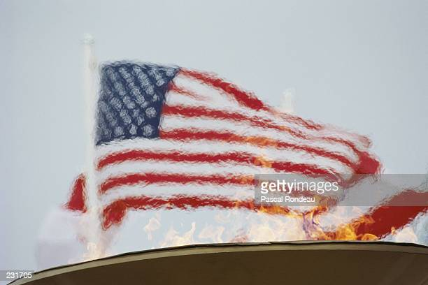 The flag of the United States flies behind the Olympic Flame during the 1988 Winter Olympics in Calgary Canada Mandatory Credit Pascal...